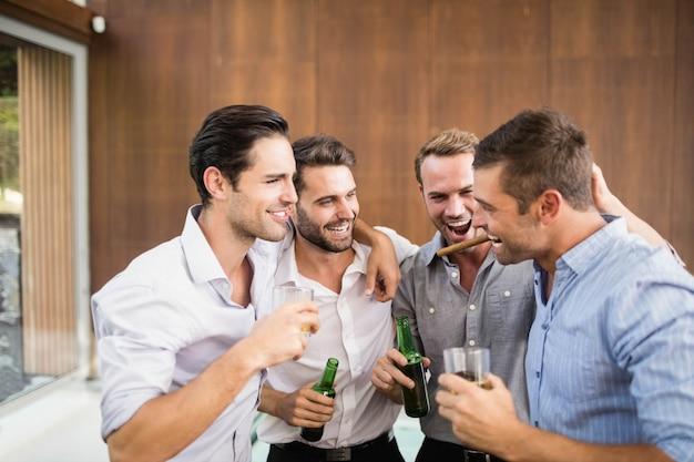 Groep jonge mannen die dranken hebben op het feest
