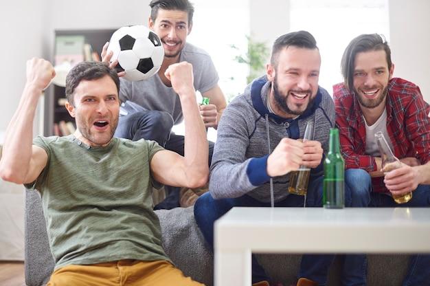 Groep jonge mannen kijken naar een wedstrijd op tv
