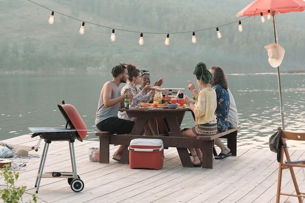 Groep jonge mensen aan de tafel zitten en lunchen tijdens picknick op een pier buiten
