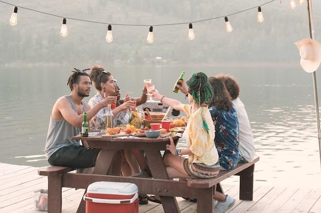 Groep jonge mensen aan de tafel zitten en samen lunchen op een pier buiten