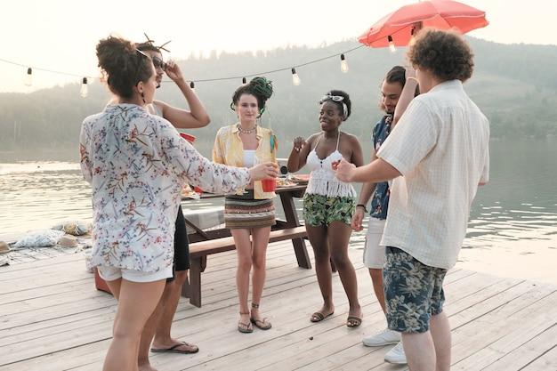 Groep jonge mensen dansen op een pier op het feest