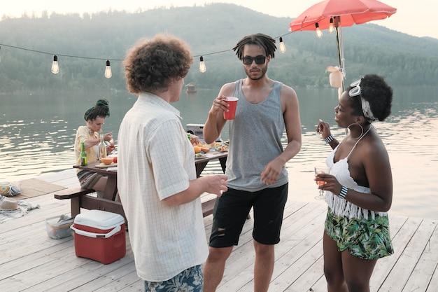 Groep jonge mensen die cocktails drinken en met elkaar praten terwijl ze buiten op de pier staan