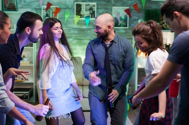 Groep jonge mensen die hun vriendschappen vieren en een feest geven in hun appartement met goede muziek.