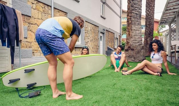 Groep jonge mensen die naar de surfinstructeur kijken in een zomerles buitenshuis. vakantie vrije tijd concept.