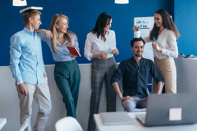 Groep jonge mensen die plezier hebben in een kantoor.