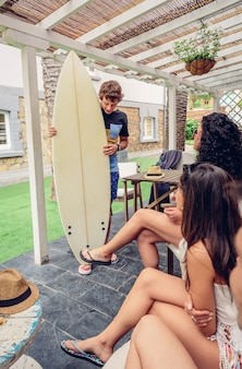Groep jonge mensen die plezier hebben in een zomerse surfles buitenshuis. vakantie vrije tijd concept.