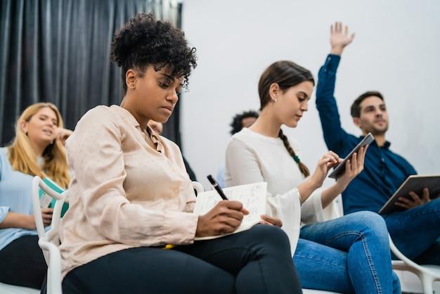 Groep jonge mensen die samen op conferentie zitten terwijl zij hun handen opsteken om een vraag te stellen. zakelijke teamvergadering seminar trainingsconcept.