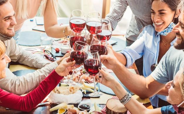 Groep jonge mensen die van tijd genieten die rode wijn drinken bij restaurant met gezichtsmasker.