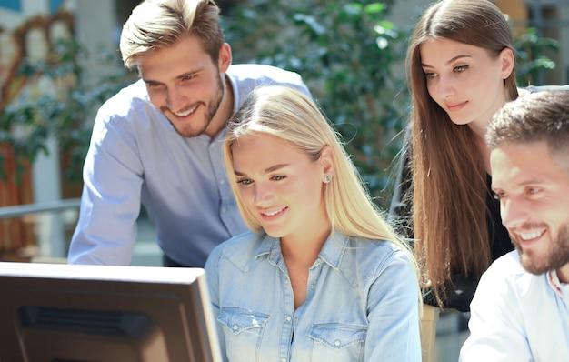 Groep jonge mensen in vrijetijdskleding die aan het bureau zitten en iets bespreken terwijl ze samen naar de pc kijken.