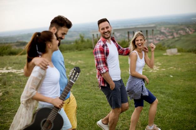Groep jonge mensen met akoestische gitaar die op het de zomergebied lopen