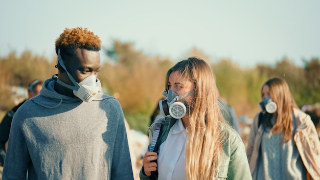 Groep jonge mensen met gasmaskers die door de giftige rook op een vuilnisbelt gaan