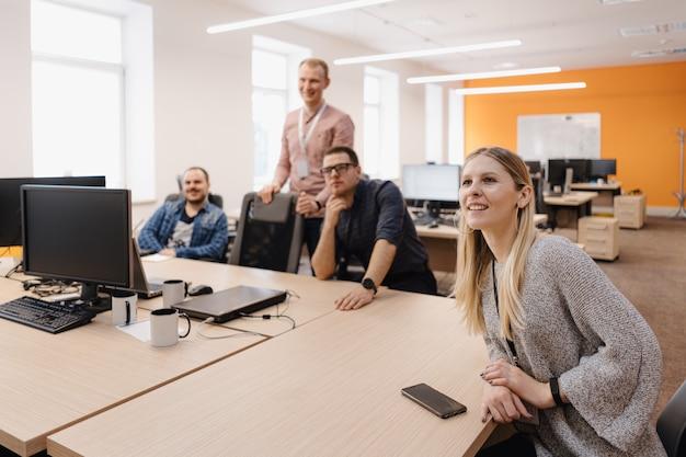Groep jonge mensen uit het bedrijfsleven die werkzaam zijn in het kantoor