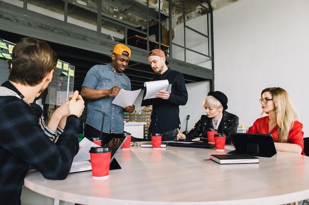 Groep jonge mensen uit het bedrijfsleven verzameld samen bespreken van creatief idee. groep internationale studenten zitten aan tafel met koffie en computers en praten