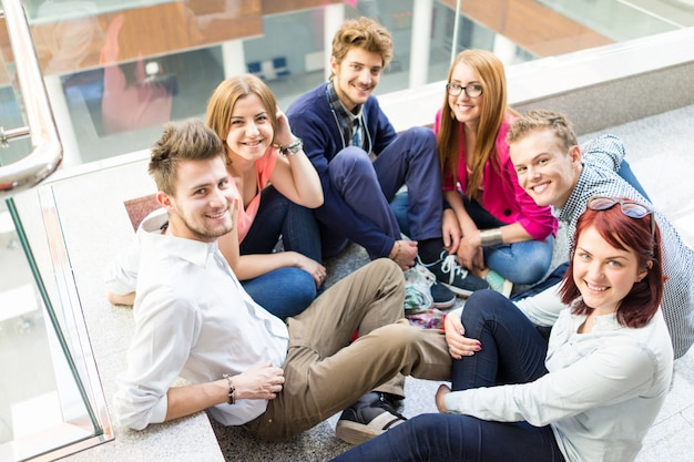 Groep jonge mensen zittend op de vloer binnenshuis