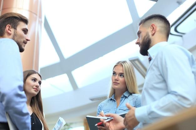Groep jonge moderne mensen in slimme vrijetijdskleding die een brainstormvergadering hebben terwijl ze in het creatieve kantoor staan.