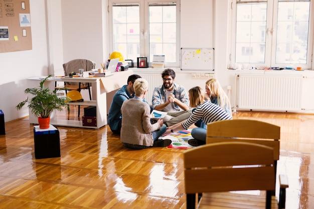 Groep jonge moderne ontwerpers die op een vloer zitten en nieuwe plannen maken.