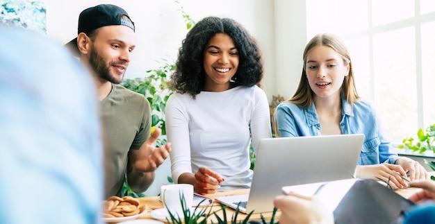 Groep jonge moderne teams in slimme vrijetijdskleding bespreken iets terwijl ze in het creatieve kantoor werken. beginnen. coworking ruimte. ondernemingsideeën
