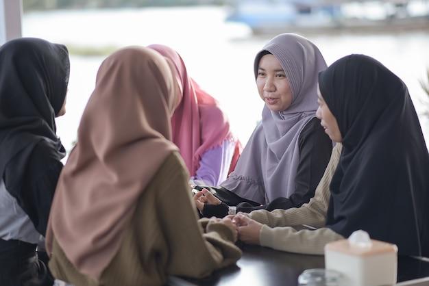 Groep jonge moslim aziatische tieners die in een café met elkaar praten