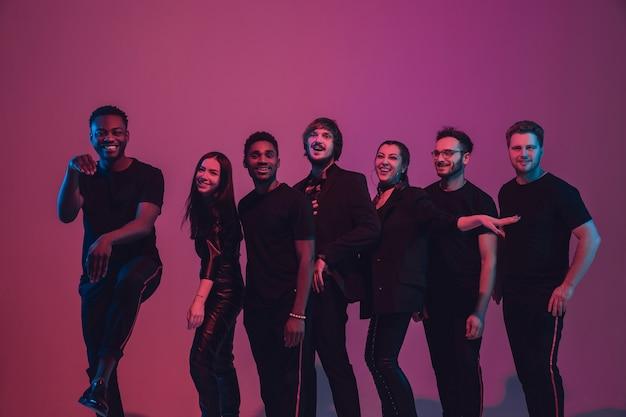 Groep jonge multi-etnische muzikanten creëerde band, dansen in neonlicht op roze achtergrond. concept van muziek, hobby, festival, wellness. vrolijke feestgastheer, danser, zanger, gitarist, saxofonist.