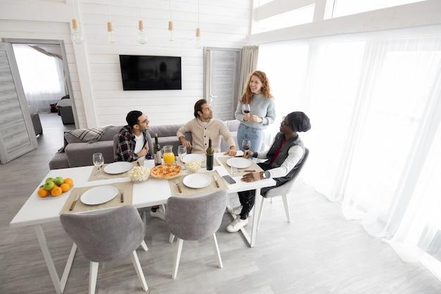 Groep jonge multi-etnische vrienden die samen samenkomen om wijn thuis te drinken