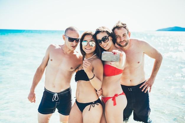 Groep jonge multi-etnische vriendenvrouwen en mannen bij het strand in zomer die selfie in het water nemen