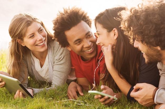 Groep jonge multiraciale mensen met digitale tablet en mobiel buiten