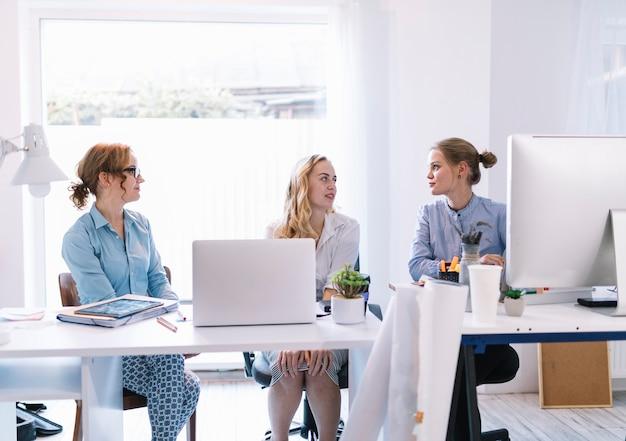Groep jonge onderneemsters die in modern bureau zitten die aan elkaar spreken
