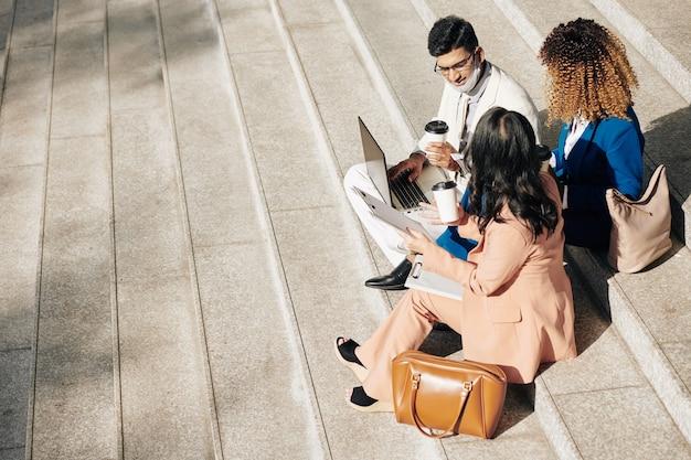 Groep jonge ondernemers die koffie drinken en projecten bespreken tijdens een buitenvergadering