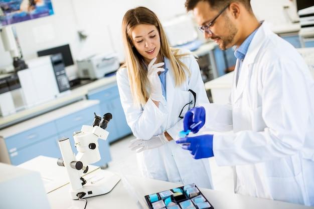 Groep jonge onderzoekers die chemische gegevens in het laboratorium analyseren