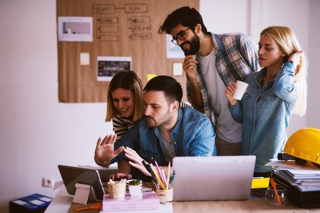 Groep jonge ontwerpers die in een bureau zitten en door wat administratie op een tablet kijken.