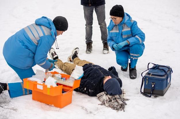 Groep jonge paramedici in winter uniform gehurkt en helpen zieke onbewuste man liggend in de sneeuw