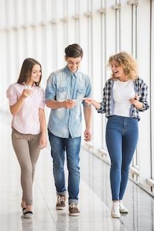 Groep jonge positieve vrienden die hun telefoons gebruiken.