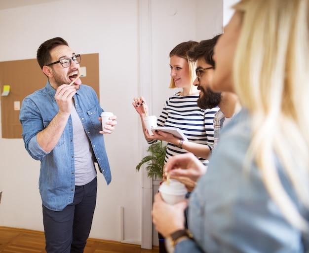 Groep jonge speelse gelukkige medewerkers die pret op onderbreking hebben terwijl samen koffie in de document kop drinkt.