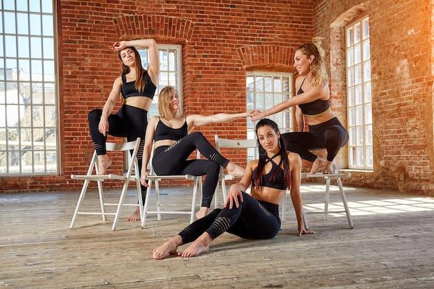 Groep jonge sportenmeisjes die na een training in een ruime zolderstudio rusten. vrouwelijke vriendschap in de sportschool, ontspannen na fitness, binnenshuis, verblinding door de zon.