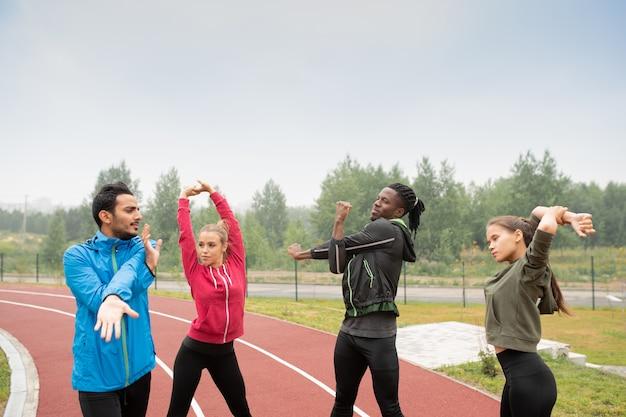 Groep jonge sportieve interculturele vrienden in activewear die opwarmingsoefeningen op stadion doen alvorens marathon te lopen
