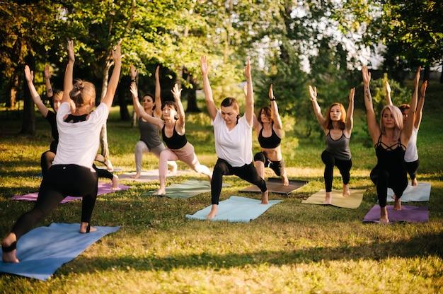 Groep jonge sportieve knappe vrouwen die yogales beoefenen met instructeur in stadspark op zonnige zomerochtend. groep mensen staat samen in virabhadrasana 1-oefening, warrior één pose