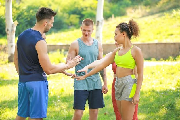 Groep jonge sportieve mensen die handen in openlucht samenstellen