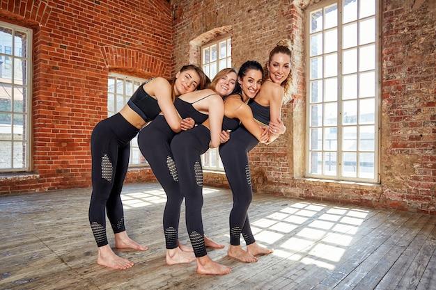 Groep jonge sportmeisjes die na een training in een ruime zolderstudio rusten