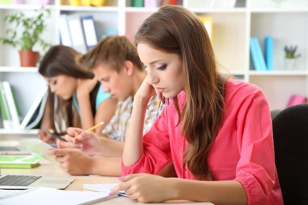 Groep jonge studenten die bij de bibliotheek zitten