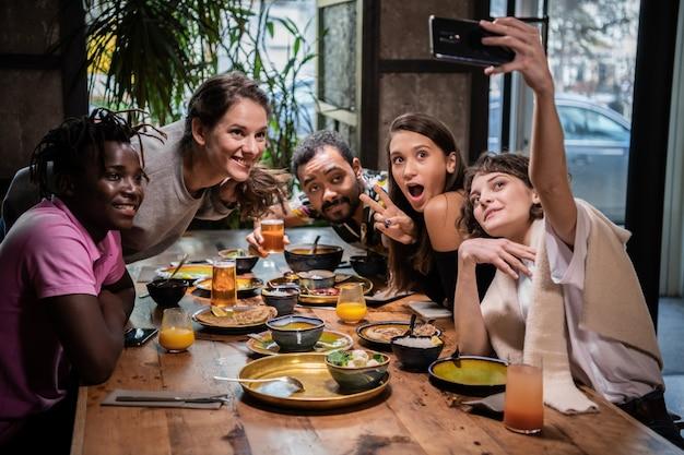 Groep jonge studenten die grappige gezichten maken, die selfies met de smartphone nemen