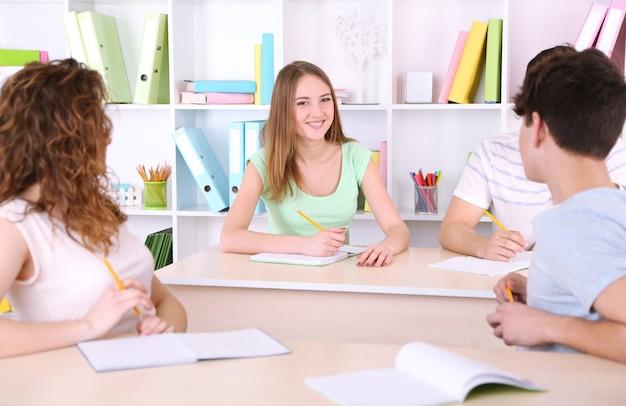 Groep jonge studenten die in de klas zitten