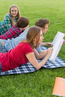 Groep jonge studenten die in park leren