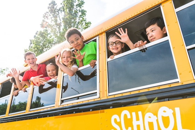 Groep jonge studenten die naar de basisschool gaan in een gele schoolbus - basisschoolkinderen hebben plezier