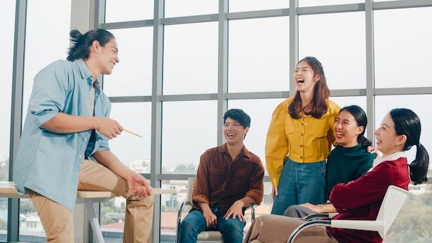 Groep jonge studenten in slimme vrijetijdskleding op de campus. vrienden brainstormen vergadering praten en bespreken werk ideeën nieuw ontwerpproject in moderne kantoren. collega teamwork, opstarten concept.