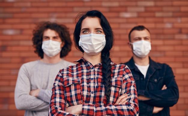 Groep jonge studenten in vrijetijdskleding en medische maskers die met gekruiste armen tegen een rode bakstenen muur staan en wegkijken met serieuze gezichten