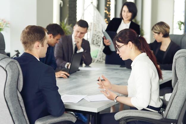 Groep jonge succesvolle zakenliedenadvocaten die samen in een vergaderruimte communiceren terwijl ze aan een project werken