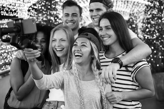 Groep jonge volwassen vrienden die een groep selfie met een selfiestok nemen