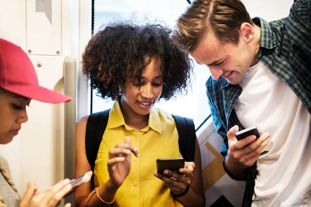 Groep jonge volwassen vrienden die smartphones in de metro gebruiken
