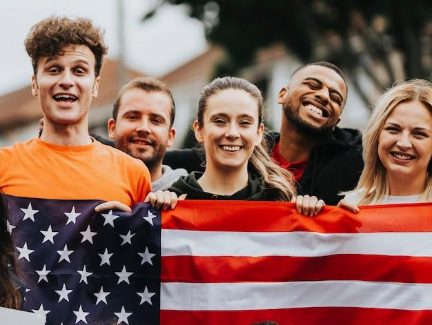 Groep jonge volwassenen die een amerikaanse vlag tonen