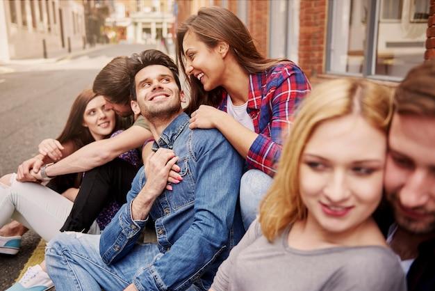Groep jonge volwassenen die op de stoep zitten
